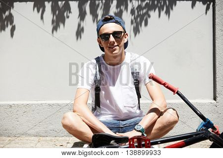 Healthy Lifestyle Concept. Teenager Wearing Glasses And Snapback Relaxing On The Sidewalks During Sh