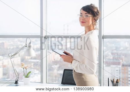 Portrait of female office manager in wearing elegant dress, using her tablet computer, standing near workplace, looking at camera
