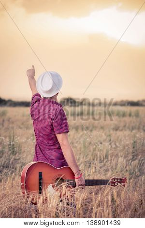 Young retro styled man holding acoustic guitar in wheat field and looking at sun to find inspiration for the next song. Music, art and lifestyle concepts.