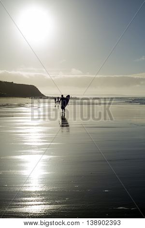 silhouette of surfer and people out for a walk as the sun sets in Ballybunion county Kerry Ireland