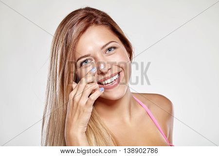 Attractive girl puts on nose cream and smiles. The gray background.