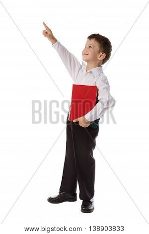 Little preschooler in casual clothing with book pointing up to empty space, isolated on white