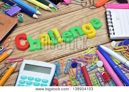Challenge word and office tools on wooden table