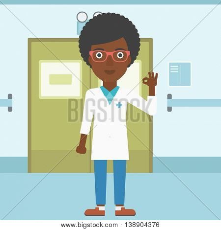 An african-american young female doctor in medical gown showing ok sign in the hospital corridor. Vector flat design illustration. Square layout.