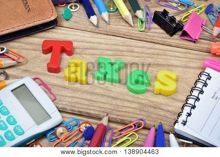 Taxes word and office tools on wooden table