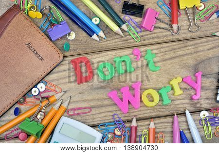 Don't Worry word and office tools on wooden table