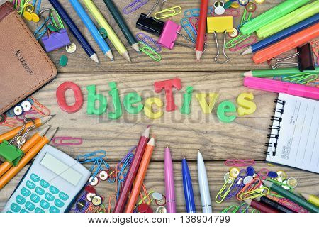 Objectives word and office tools on wooden table