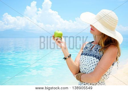 Young beautiful european woman is holding green apple in her hand against the calm soft tropical sea under blue sky on a sunny day