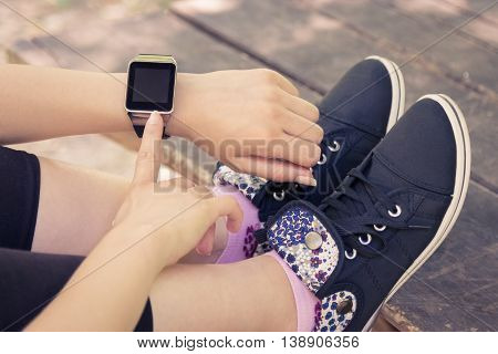 High angle view of female forefinger pressing the button on smart watch with blank screen while sitting on a bench in the park.
