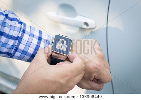 Close up shoot of male hands locking the car doors by using smart watch remote control security app.