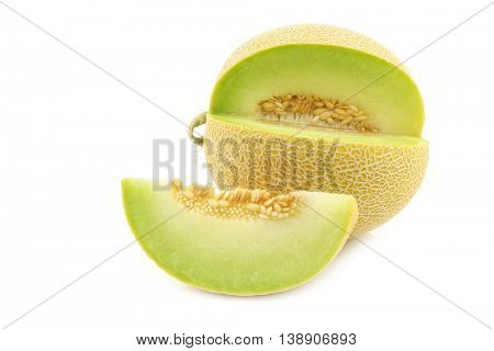 fresh galia melon and a cut piece on a white background