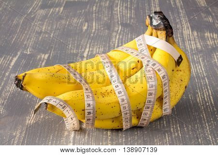Bunch of bananas with measuring tape on grey wooden background