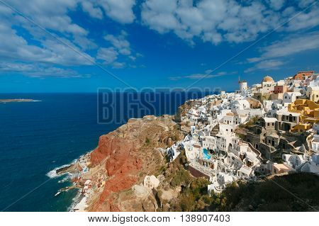 Picturesque view of windmills and white houses in Oia or Ia on the island Santorini, Greece
