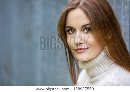 Outdoor portrait of beautiful girl or young woman with red hair wearing a white jumper
