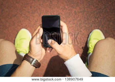 Close up of jogger hands holding smartphone with blank touch screen next to the running track. Top down point of view. Technology, sport and fitness concepts.