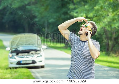Young modern stressed man making call with road assistance service by using smartphone. Car with raised hood at the roadside in the background.