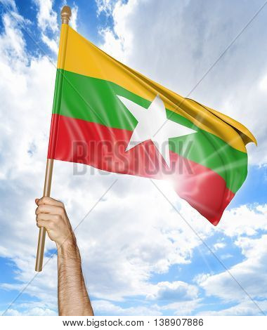 Person's hand holding the Myanmar national flag and waving it in the sky, 3D rendering