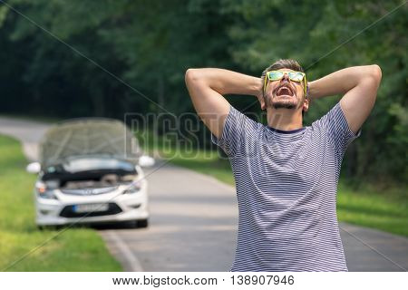 Stressed and frustrated driver pulling his hair while standing on the road next to broken car. Road trip problems and assistance concepts.