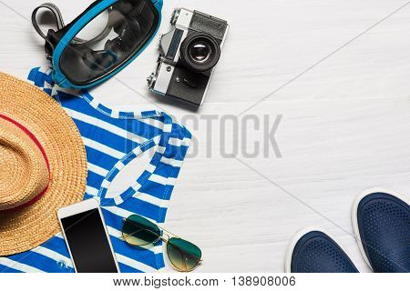 The travel and clothing accessories apparel along for the men on white wooden background. The travel, tourism and holidays concept