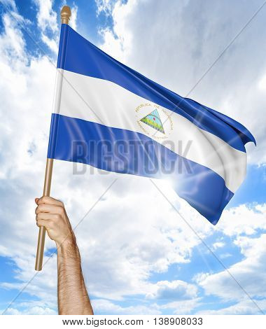 Person's hand holding the Nicaragua national flag and waving it in the sky, 3D rendering