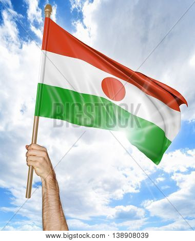 Person's hand holding the Niger national flag and waving it in the sky, 3D rendering