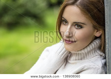 Outdoor portrait of beautiful thoughtful girl or young woman with red hair wearing a white jumper