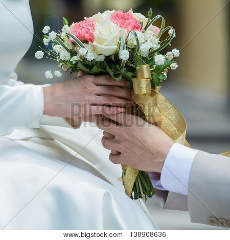 Asian lovers' hands holding vintage flower with bokeh