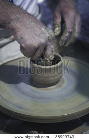 Artisan hands making clay pot on a potter's wheel.