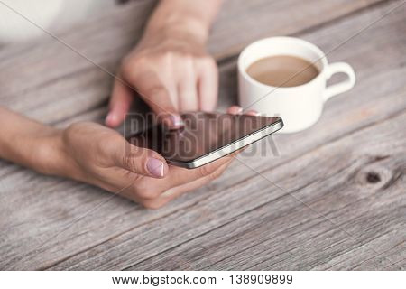 Female hand using black phone with blank screen.