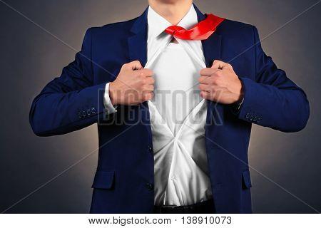 Young businessman super hero on dark background