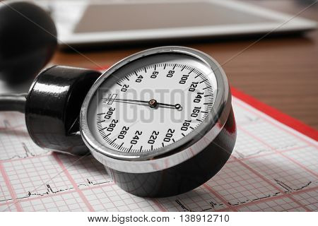 Medical concept. Medical manometer on a cardiogram, close up