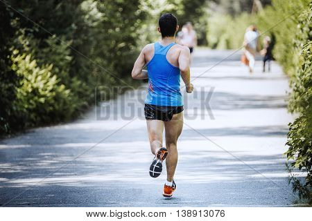 back view running male athlete on the road in summer Park during marathon