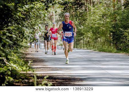 Chelyabinsk Russia - July 9 2016: old athlete man running ahead of group of runners during Summer half marathon