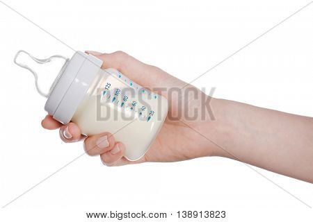 Female hand holding a baby bottle of milk on white background