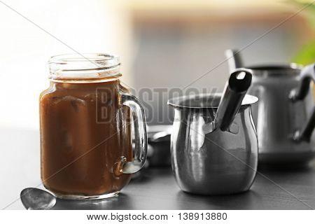 Iced coffee and metallic turk on black table