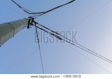 pole with wires attached to it intersect at different angles against the blue sky