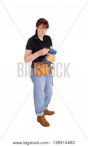 A tall woman standing isolated for white background preparing her drill for some home improvement work.