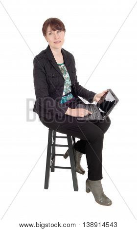 A middle age businesswoman sitting on a chair and dreaming with her laptop on her lap isolated for white background.
