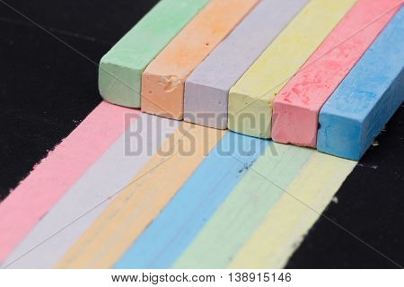 Colored chalks paint stripes of other colors. Concept of universal skills and interchangeability in team