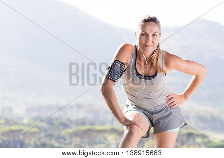 Senior female jogger resting after running in a park. Proud mature woman stretching in the park and looking at camera. Senior active woman completing her daily routine workout.