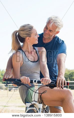 Active senior couple together riding bicycle and looking at each other. Senior smiling couple in the park riding cycle. Senior husband giving cycle ride to mature wife.