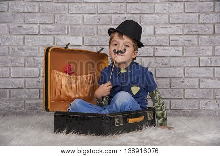 A boy having fun in the studio perched in a suitcase and wearing a hat.