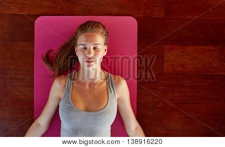Top view of beautiful young woman lying on exercise mat with her eyes closed at yoga class. Fitness female in corpse pose at gym.