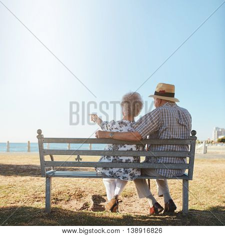 Senior Couple Sitting On Bench Looking Out To Sea
