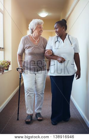 Senior Woman Walking Being Helped By Female Nurse