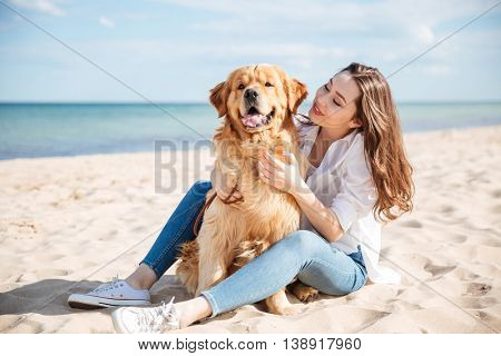Beautiful young woman sitting and having rest with her dog on the beach
