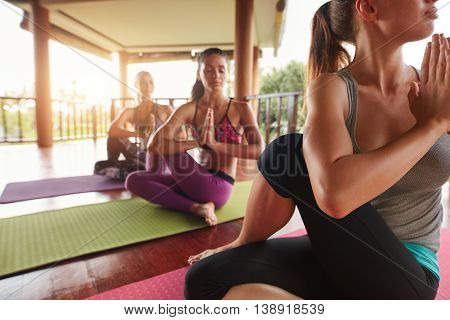 Young People Practicing Yoga In Spinal Twist Pose