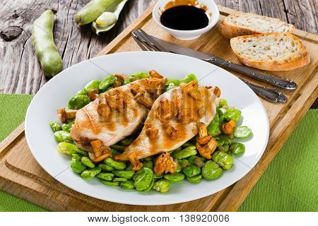 grilled chicken breast served with fried butter beans chanterelles and shallot on dish on cutting board with fork knife bread with seeds and soy sauce view from above close-up