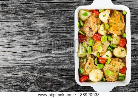 dish with stewed chicken meat new potatoes and butter lima bean on old wooden table view from above blank space left