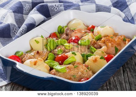 oven baked juicy chicken meat with new potatoes tomatoes and butter lima beans in dish on old wooden table with kitchen cloth view from above close-up